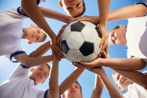 Low angle view of boys in junior football team standing in circle holding ball together against  blue sky, focus on ball
